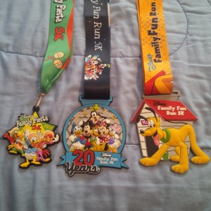 "Walt Disney World Family 5k ""medals"" from 2012, 2013, and 2014"