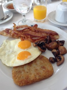 Breakfast: Two eggs, sunny-side up, American bacon, hash brown and sauteed mushrooms