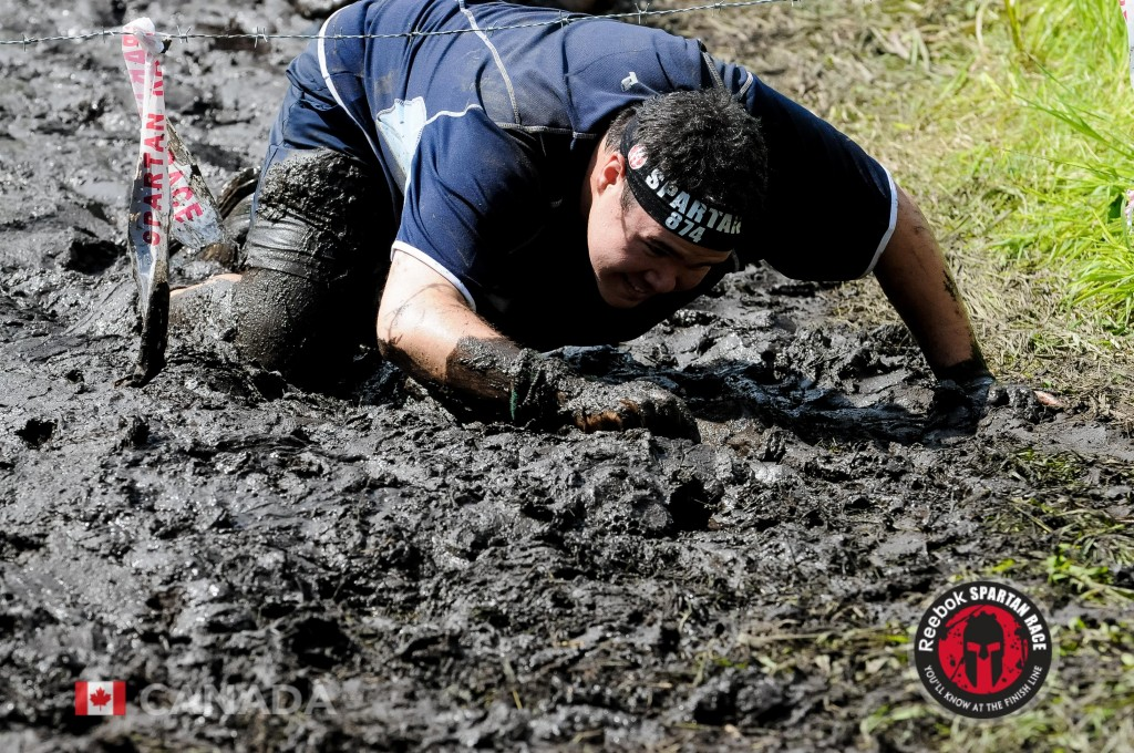 Official Race photo of me crawling under barbed wire through mud at the Toronto Sprint Spartan Race