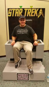 In a Star Trek captain's chair made of Mega Blocks. It's a shame I had the wrong shirt on...